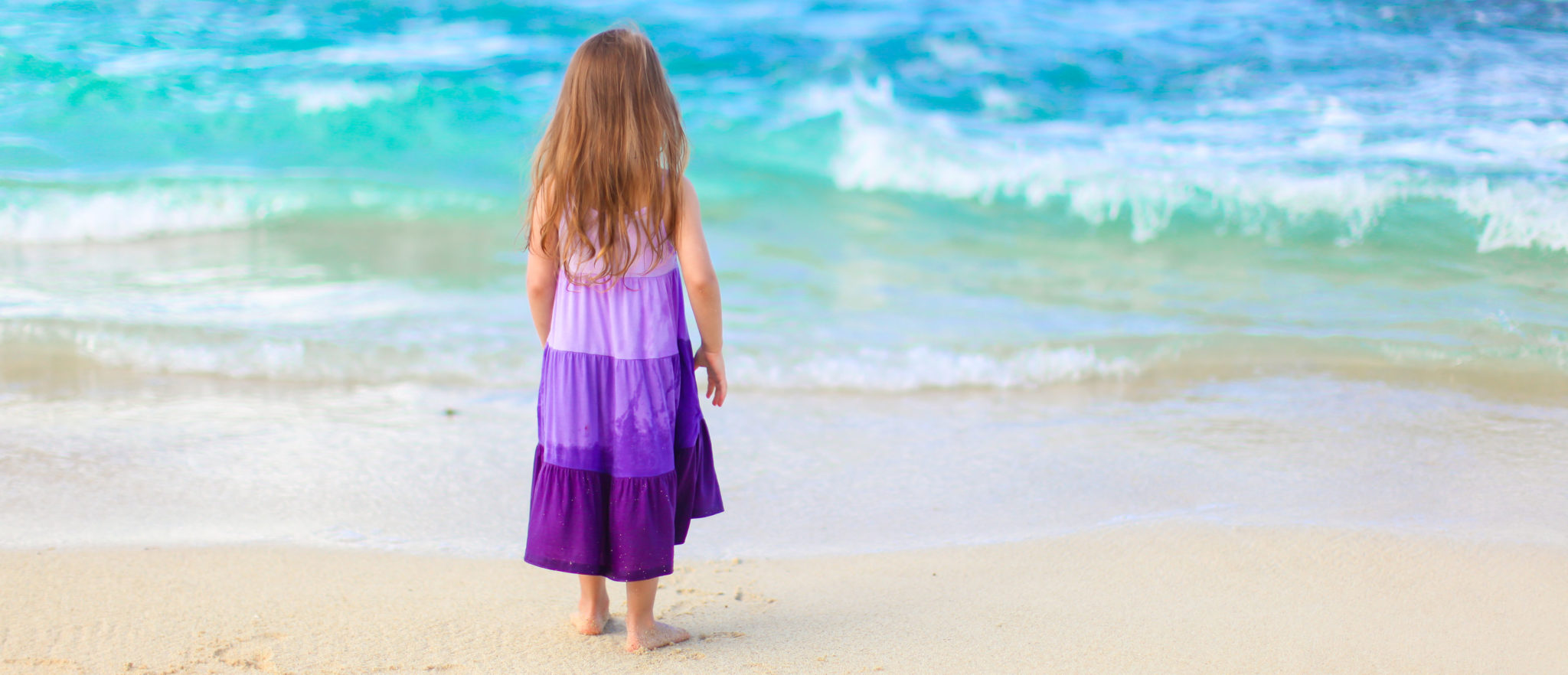 Petite fille qui s'ennuie sur la plage
